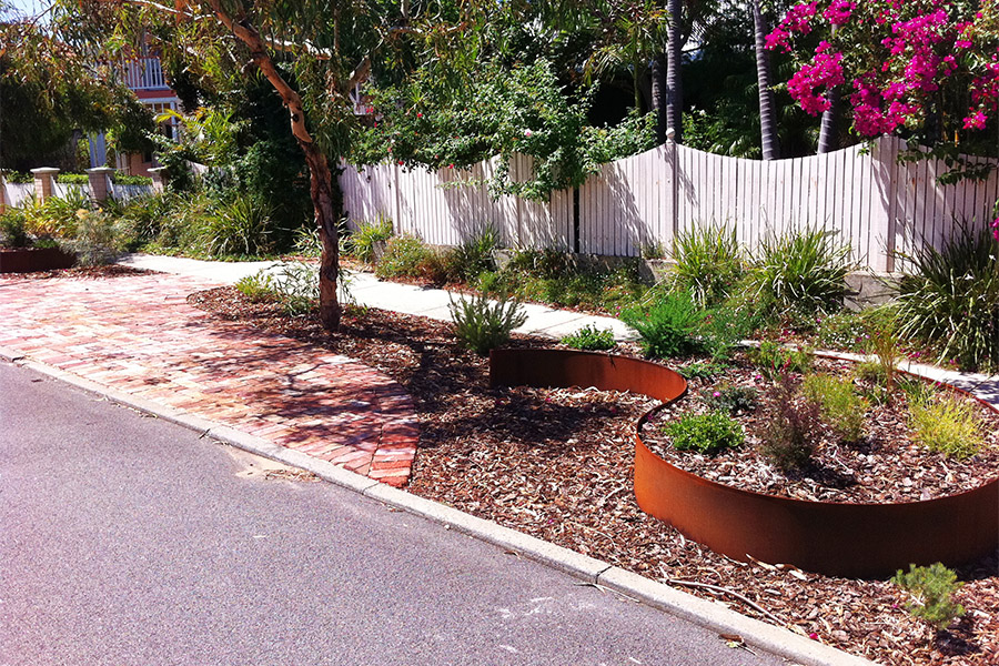 Verge garden with rusted metal feature planters